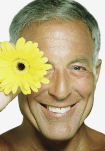 Mature man holding a sunflower by his face