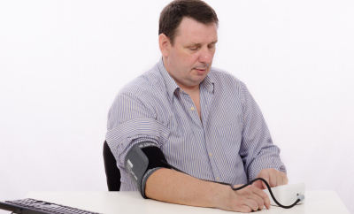Middle aged man with blood pressure machine