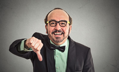 Happy guy showing thumbs down hand gesture on grey background